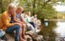 Multi-generational family relaxes by the water and collects rocks - just one of many family staycation ideas for summer fun.
